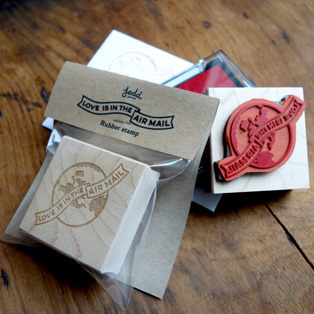 "Rubber stamp and packaging, with a globe design that reads ""Love is in the Air Mail"""