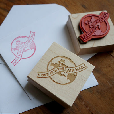 "Rubber stamp and envelope, with a globe design that reads ""Love is in the Air Mail"""