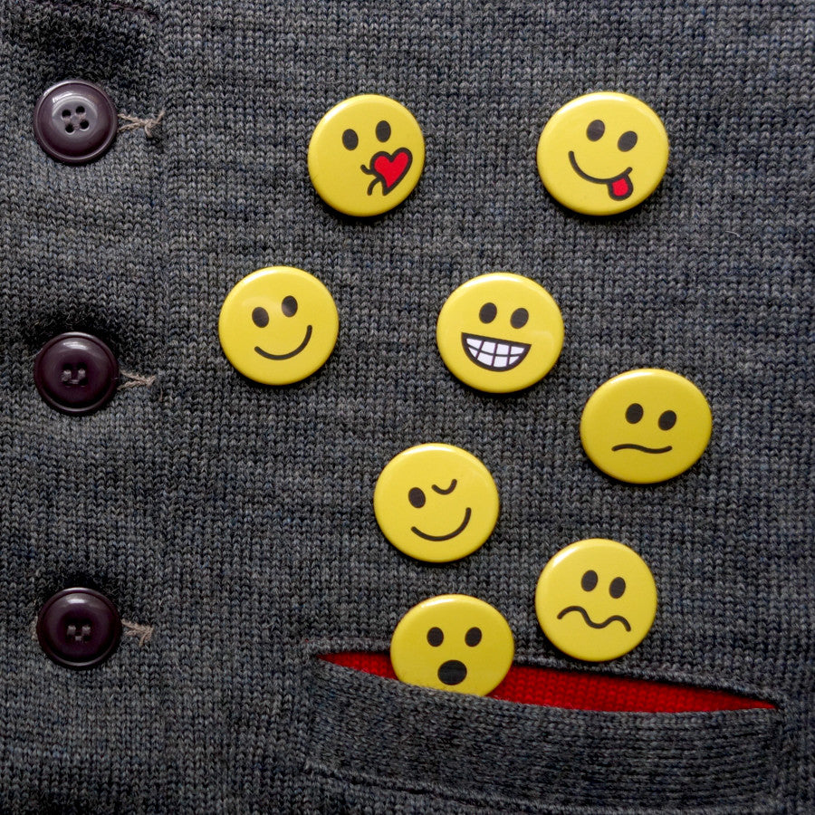 A collection of small pin buttons with different emotional faces
