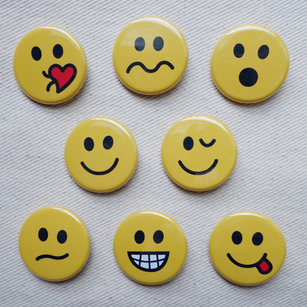 Detailed picture of small pin buttons with different emotional faces