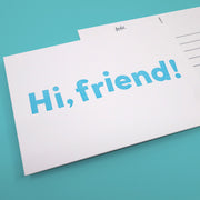 "A white postcard that reads ""Hi, friend!"""