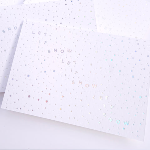 "A photo of a greeting card reading ""Let it snow, let it snow, let it snow"""