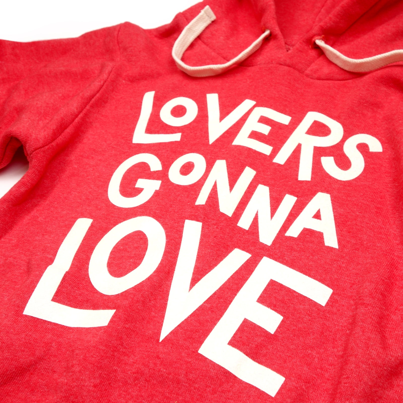 "Detail of a red hooded sweatshirt with white letters reading ""Lovers Gonna Love"""