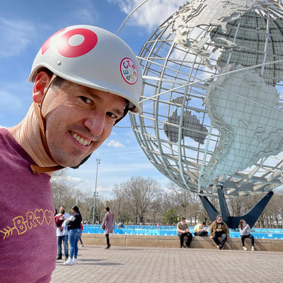 A photo of Jedd wearing a bike helmet with XO and the Unisphere, a globe sculpture, in the background