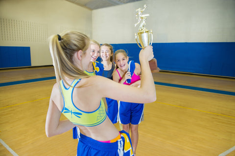 teen athletes pose with a trophy in their Dragonwing girlgear sports bras.