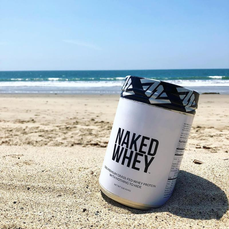 Tub of Unflavored Naked Whey in the sand in front of the sea