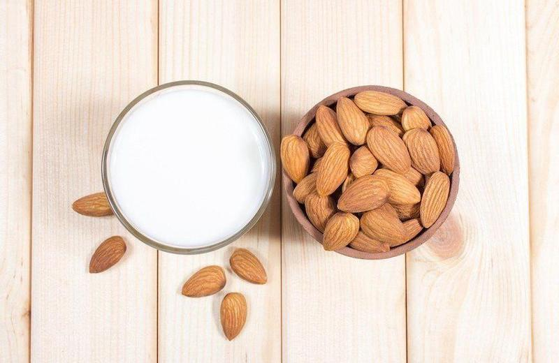 Glass of almond milk next to a bowl of almonds