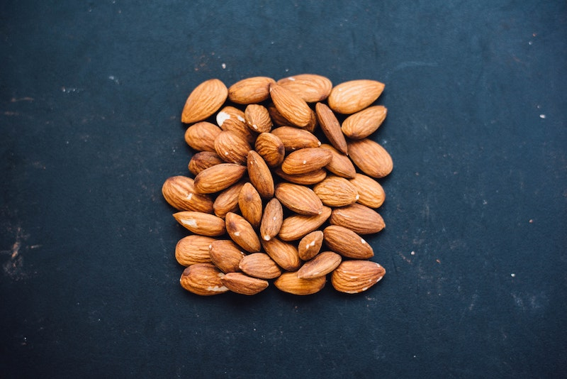 Pile of almonds placed into the shape of a square against a dark blue background