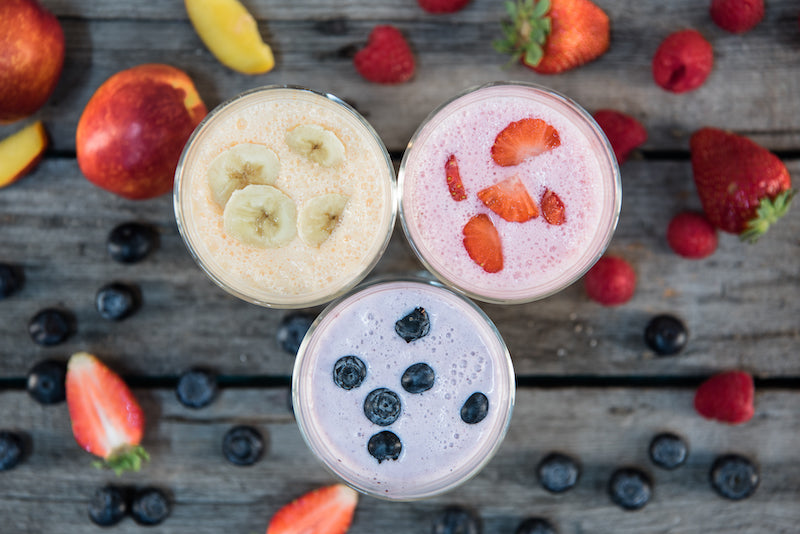 Three different flavored protein smoothies surrounded by pieces of cut up fruit