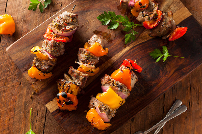 Beef and vegetable kebabs rolled in powdered peanut butter on a wooden chopping board