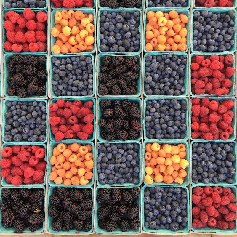 Aerial view of many different punnets of berries, ranging from raspberries to blueberries