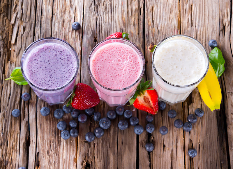 Three different flavored breakfast protein shakes, flavored with various berries