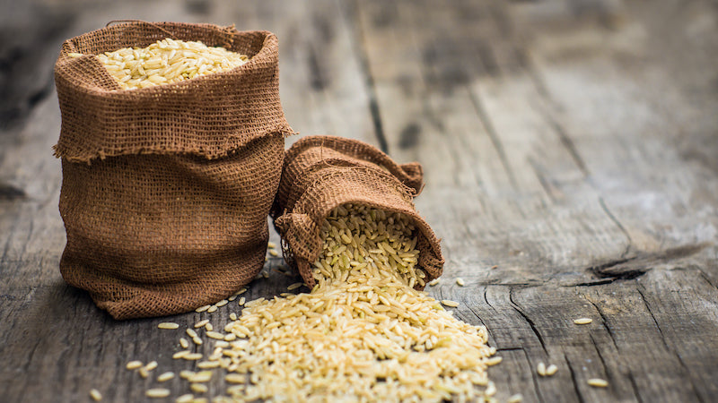 Two woven bags of brown rice grains, one on it's side with the rice spilt on the wooden counter