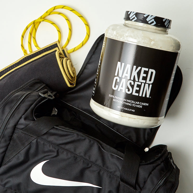 Tub of Naked Casein next to a gym bag, skipping rope, and a gym mat