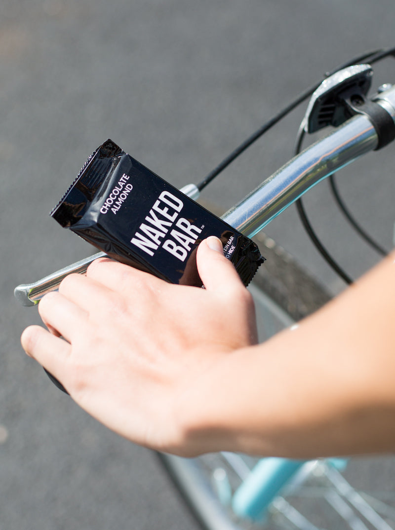 Close up of a bike's handlebars while somebody is holding a Naked Nutrition Naked Bar