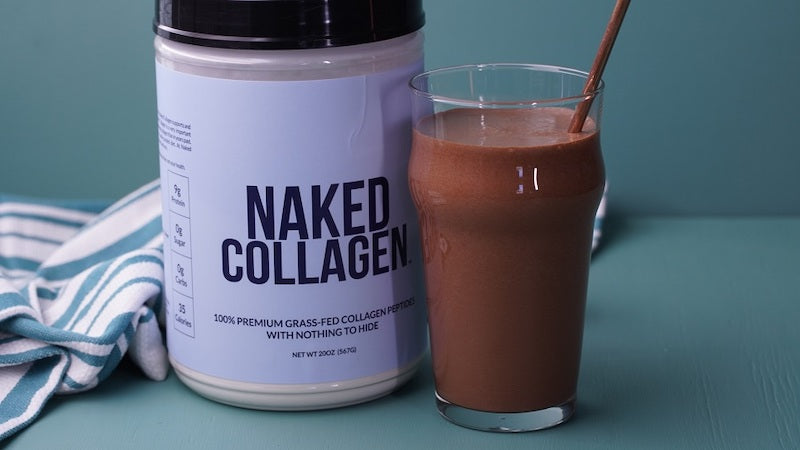 Tub of Naked Collagen next to a chocolate collagen shake