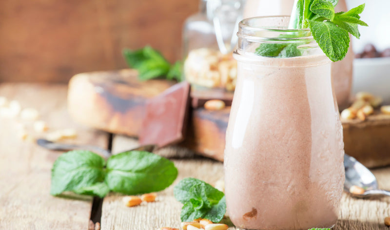 Mint chocolate protein shake in a glass bottle on a wooden table