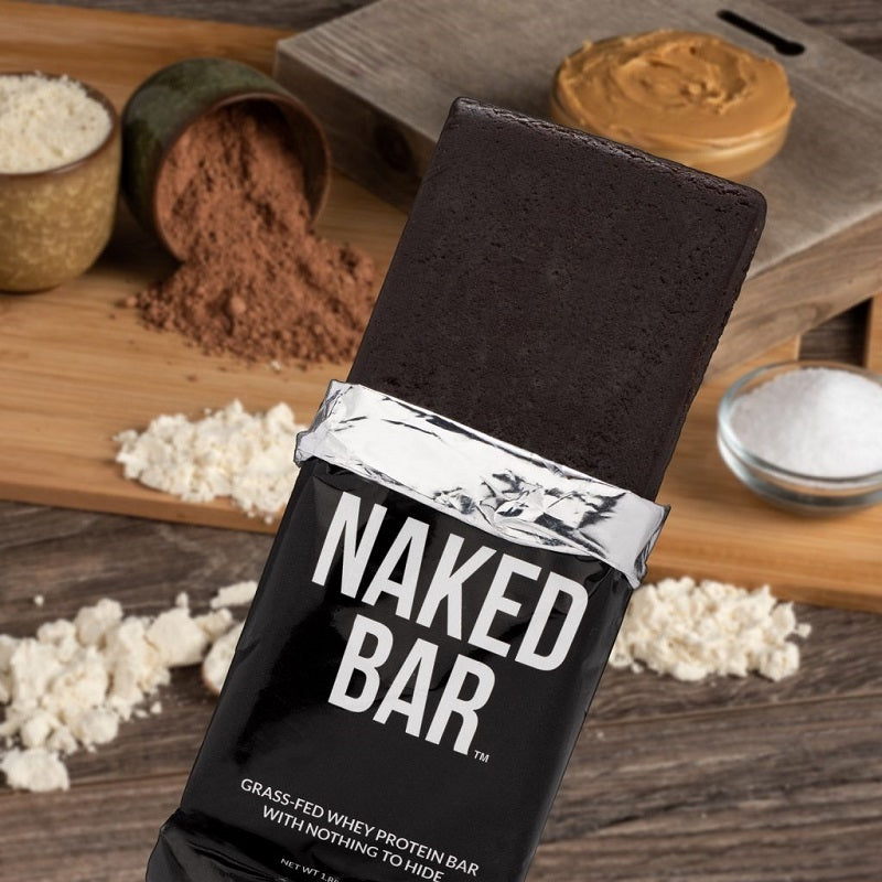Naked Bar product image with the bar in front of various ingredients contained in the bar in the background