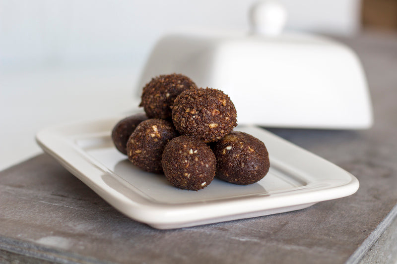 Chocolate peanut butter protein bites on a white china tray