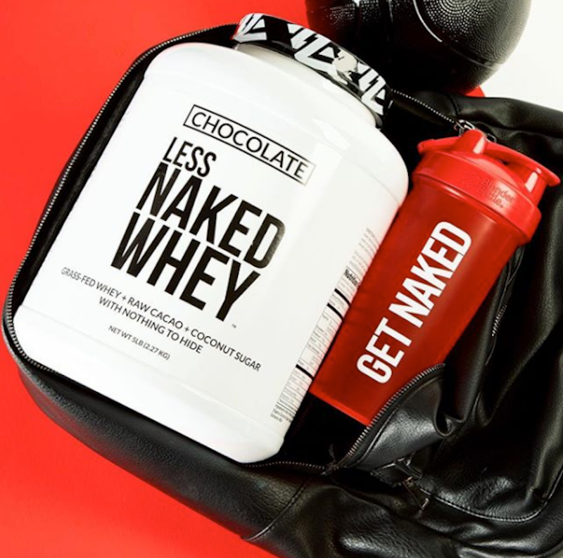 Chocolate Naked Whey tub in a gym bag next to a Naked Nutrition shaker bottle