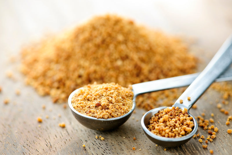 Pile of coconut sugar next to two spoons of coconut sugar