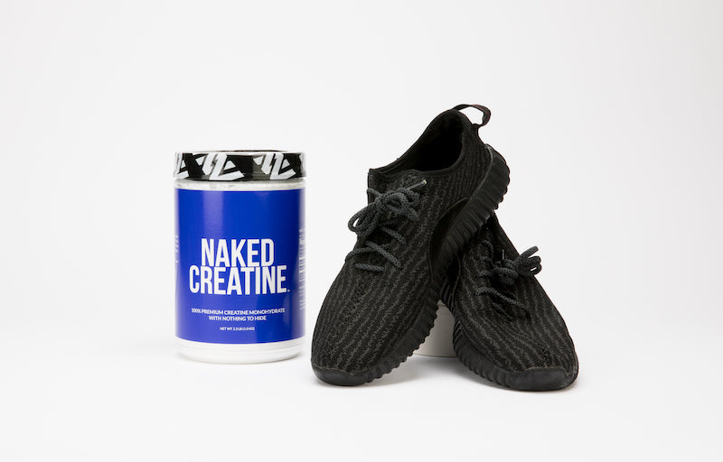 Tub of Naked Creatine next to a pair of black gym shoes against a white background