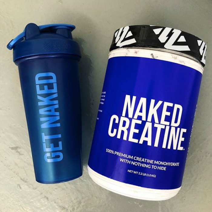 Tub of Naked Creatine next to a Naked Nutrition blender bottle