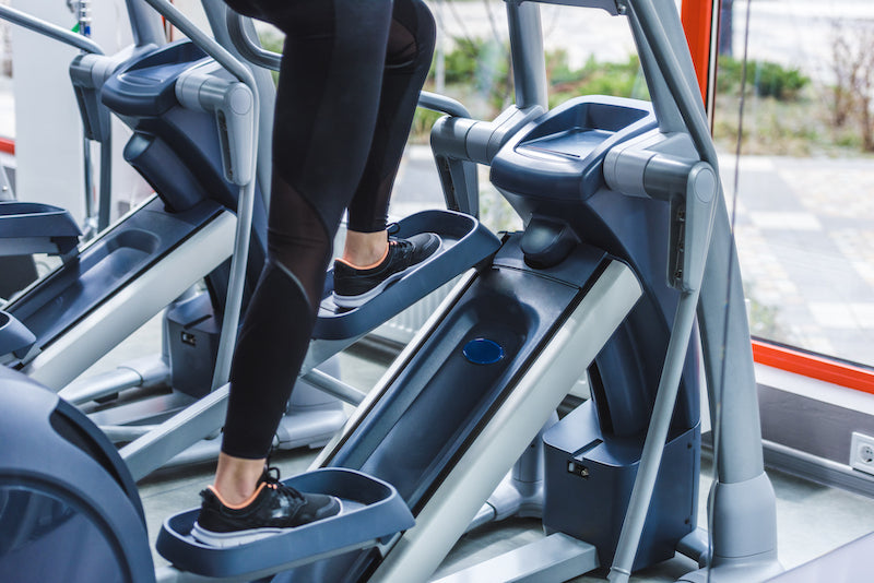 Cropped image of a woman working out on an elliptical machine in a gym