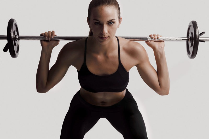 fit young woman doing a back squat