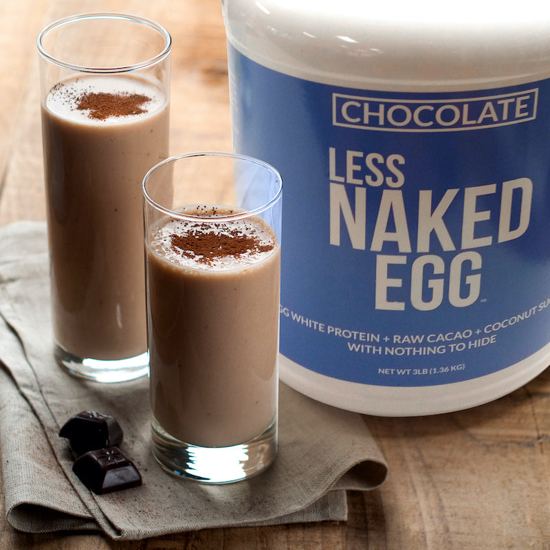 Tub of Chocolate Naked Egg next to two chocolate flavored protein shakes