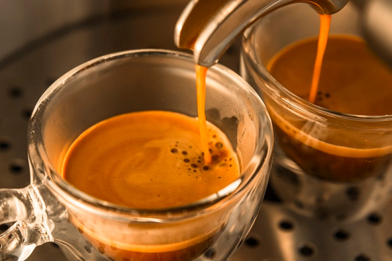 Coffee machine pouring espresso shots into glass cups