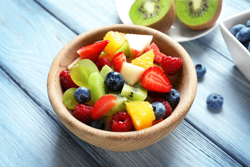 Wooden bowl of fruit salad on a wooden table