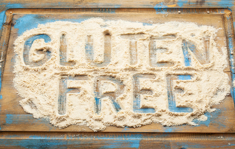 Flour on a table top with the words 'gluten free' written into it