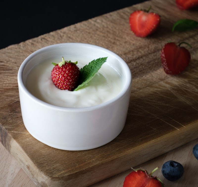 Bowl of Greek Yogurt topped with a single strawberry on a wooden board