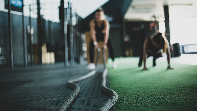 People working out in a gym using battle ropes
