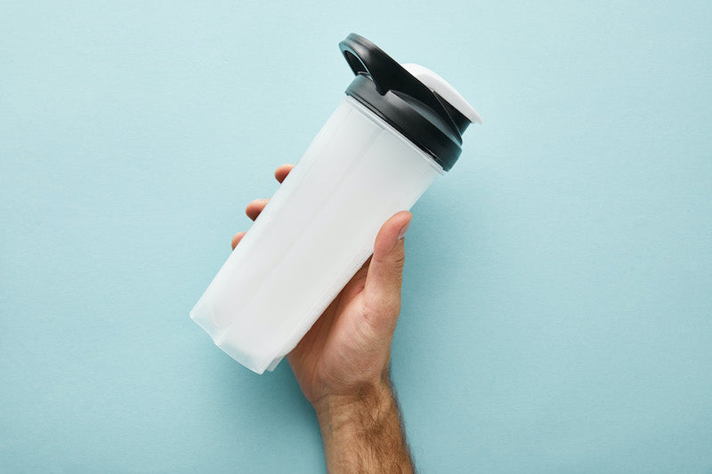 Hand holding protein shake against a blue background