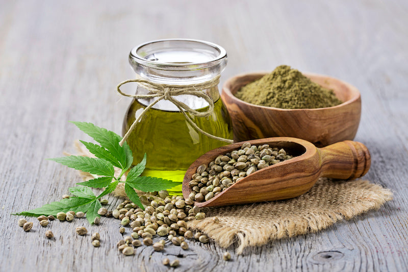 Hemp oil in a glass jar, a bowl of hemp powder, and a scoop of hemp seeds on a wooden table