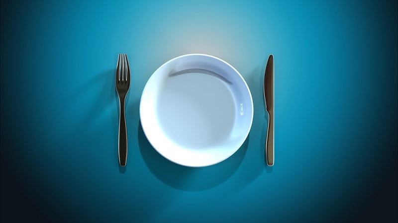 Empty plate next to a knife and fork against a blue background