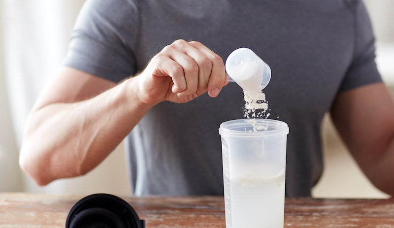 Man pouring a scoop of creatine into a shaker bottle with water