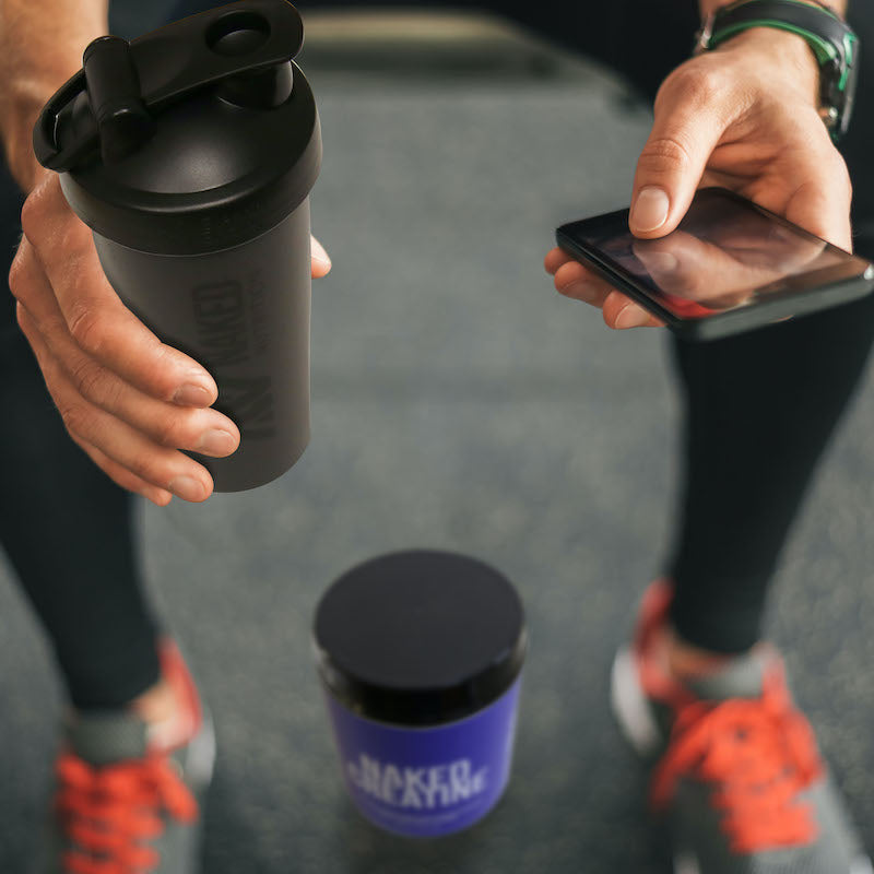 Man sitting down in the gym on his phone, a tub of Naked Creatine is on the floor between his shoes