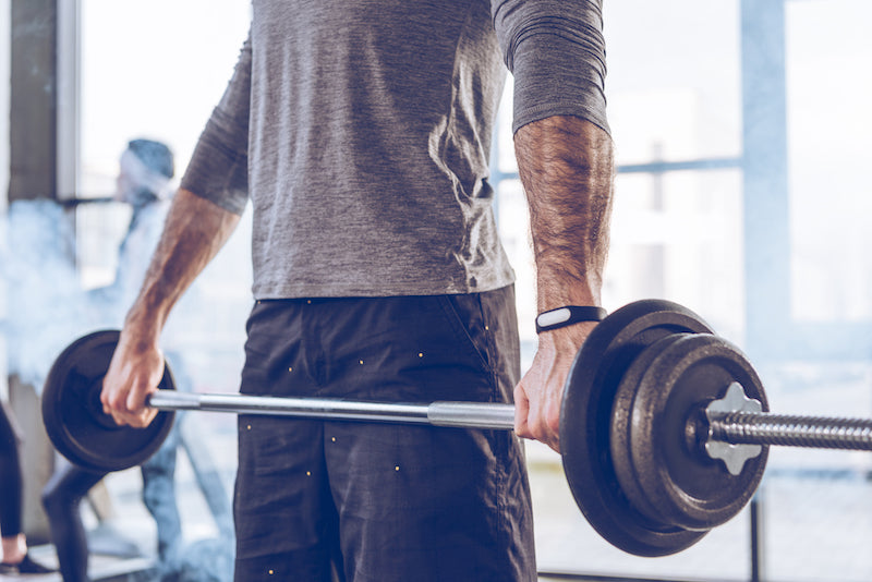 Man picking up a barbell in a gym setting