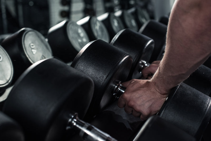 Person picking up dumbbells from a weight rack in a gym setting