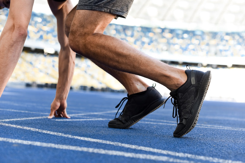 Man exercising in a stadium, in a ready position to start running