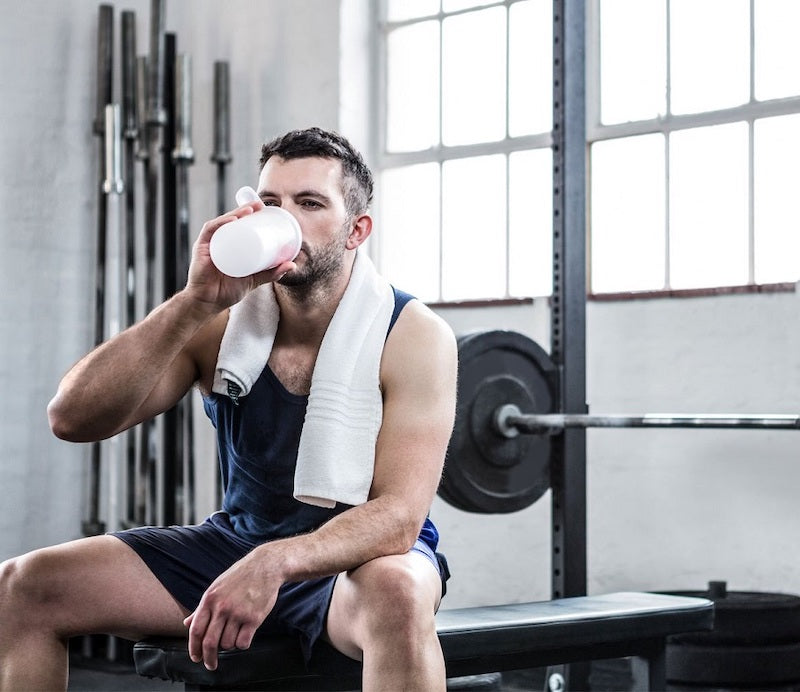 Man sitting in a gym drinking a protein shake