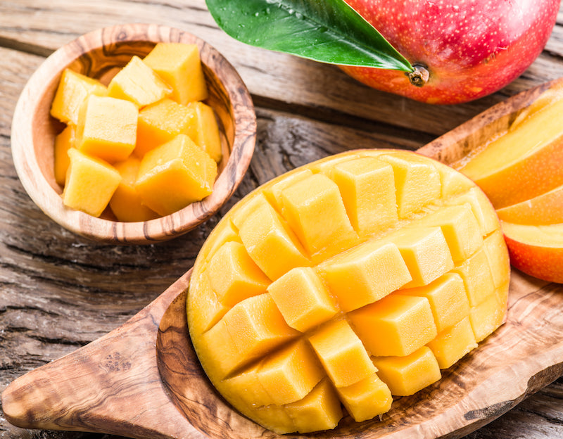 Cut up mango slices on a wooden board