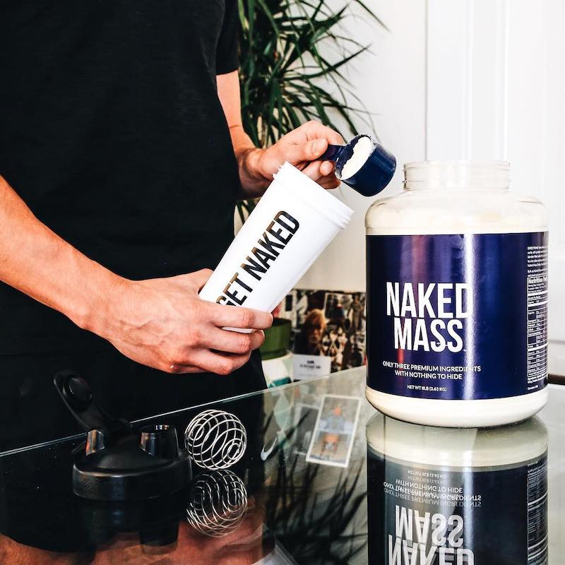 Naked Mass product image with a man putting a scoop of Naked Mass into a Naked Nutrition shaker bottle