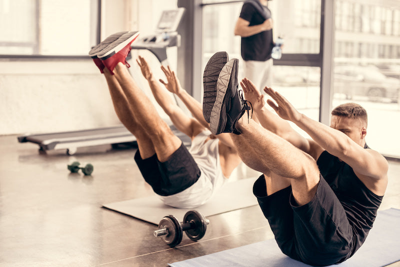 Two men doing exercises on gym mats in a gym hall