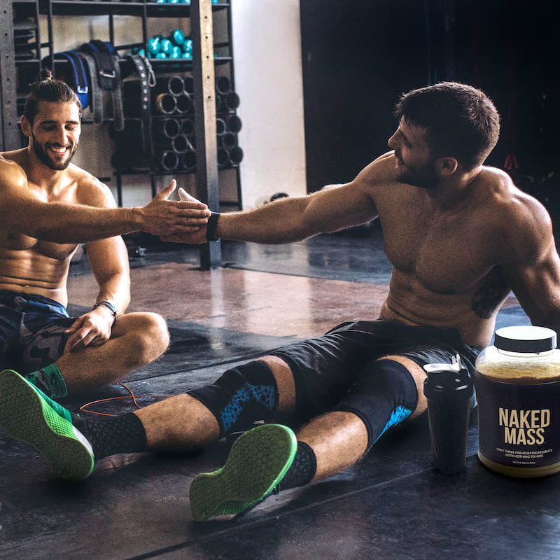 Two men sitting down and resting after a workout in the gym, a tub of Naked Mass is next to them
