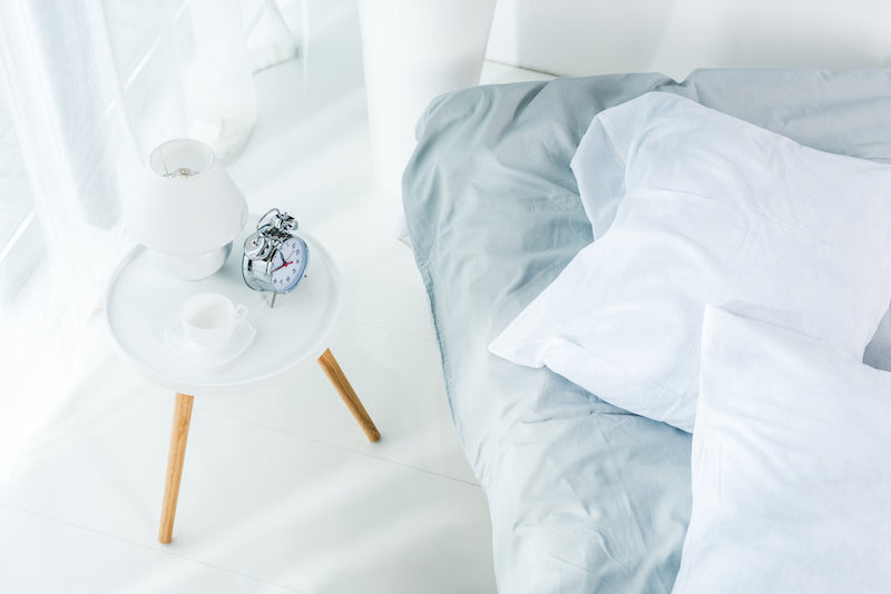 Unmade bed next to a bedside table with a typical alarm clock