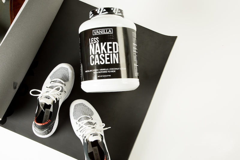 Tub of Vanilla Naked Casein on a workout mat next to a pair of gym shoes